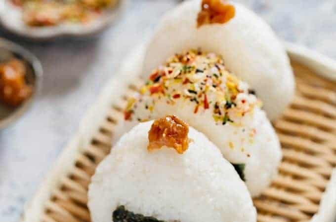 Three onigiri rice balls two with pickled plum topping and one with Furikake sprinkled on a bamboo tray