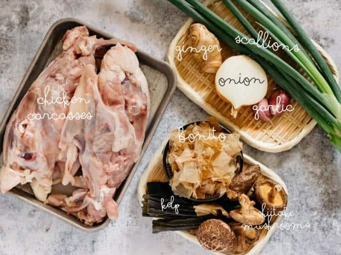 chicken carcassses, ginger, onion, garlic, scallions, bonito flake, kelp and shiitake mushrooms on bamboo trays