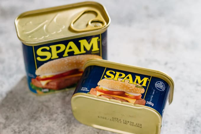 a normal size Spam on the left and smaller size tin of Spam on right front