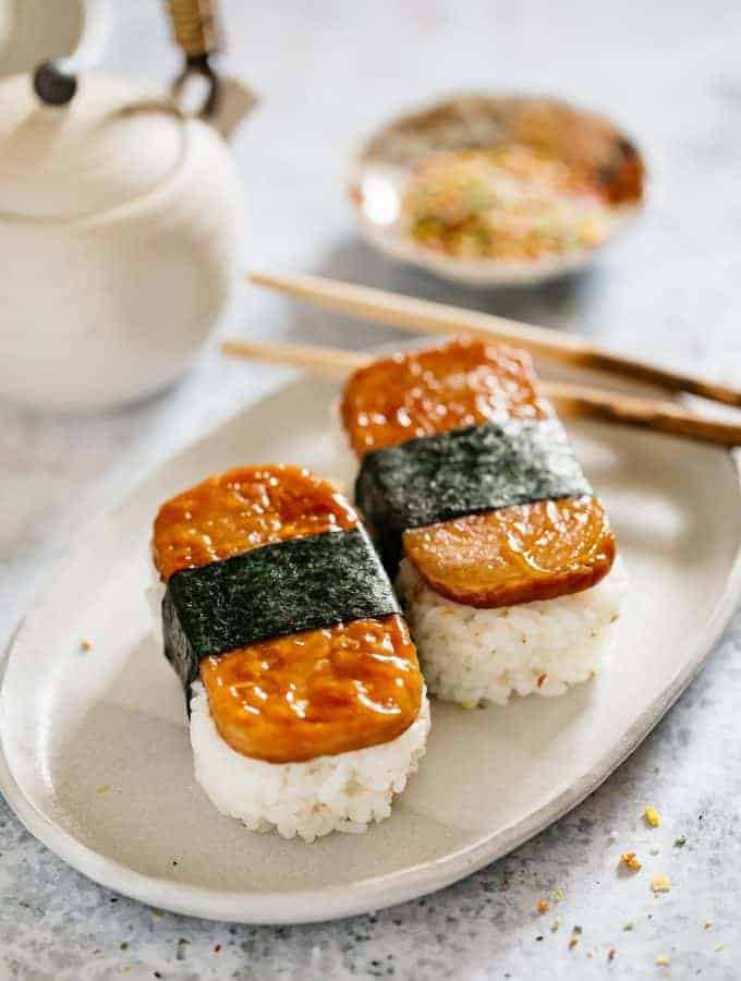 two spam musubi served on an oval shaped plate, a pair of chopstick