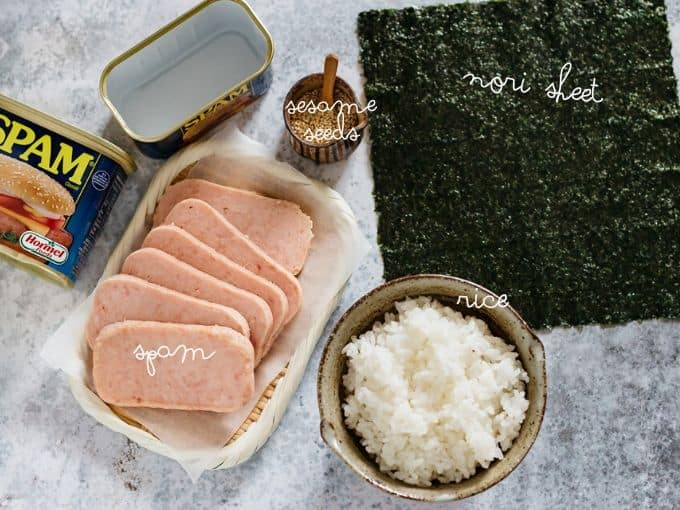 Slices spam on a plate and an empty tin, a Nori sheet,  sesame seeds and a bowl of rice