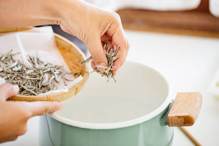 adding dried infant anchovies into a stock pot