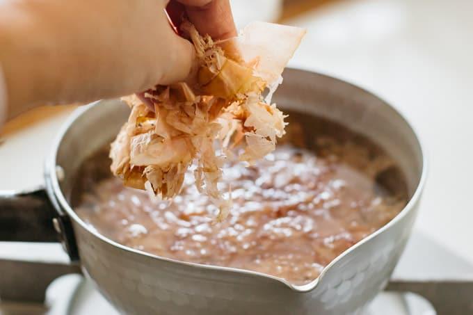 Adding kezuribushi into a large saucepan