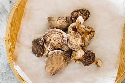 many dried shiitake mushrooms on a bamboo tray