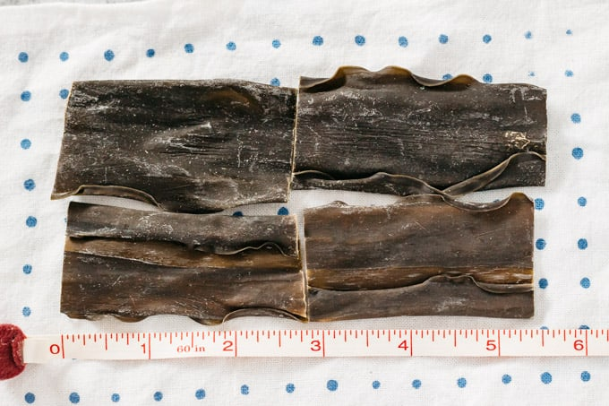 4 pieces of Kombu kelp with measuring tape showing length about 5.5 inches