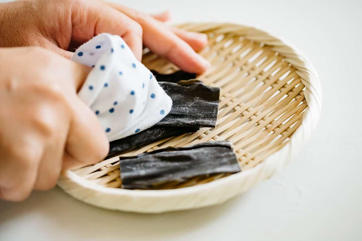 wiping dried kombu kelp with a clean cloth