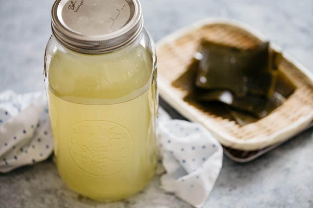 Kombu dashi in a large jar with kombu kelp on a bamboo tray in background