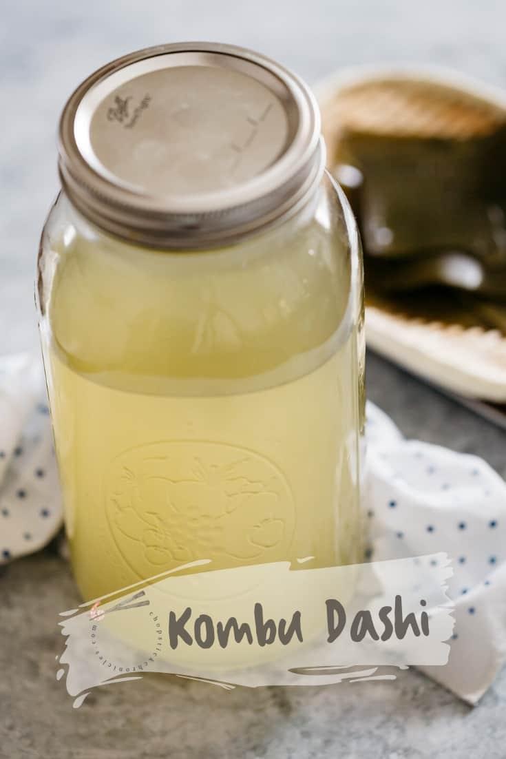 Kombu dashi in a large storing jar with kombu kelp on a bamboo tray in background