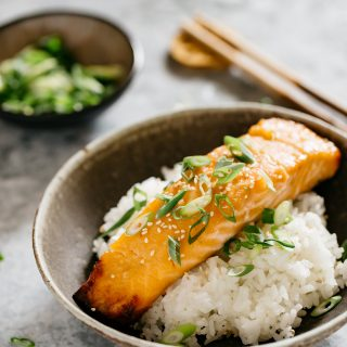 a piece of Miso glazed salmon served on bed of plain cooked rice in a shallow bowl.