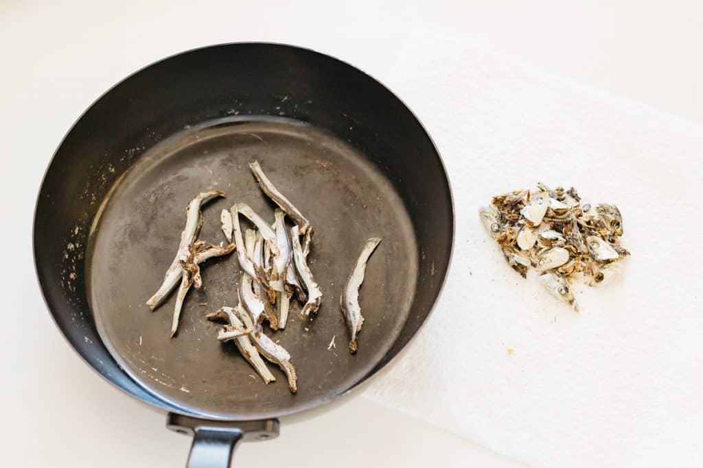 dried anchovy the heads removed in a frying pan and heads on the right on kitchen paper