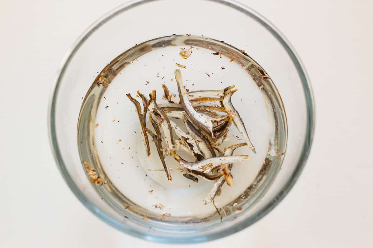 dried anchovies submerged under water in a large bowl
