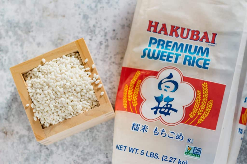 glutinous rice packet on the right and rice in a wooden cubic container on the left