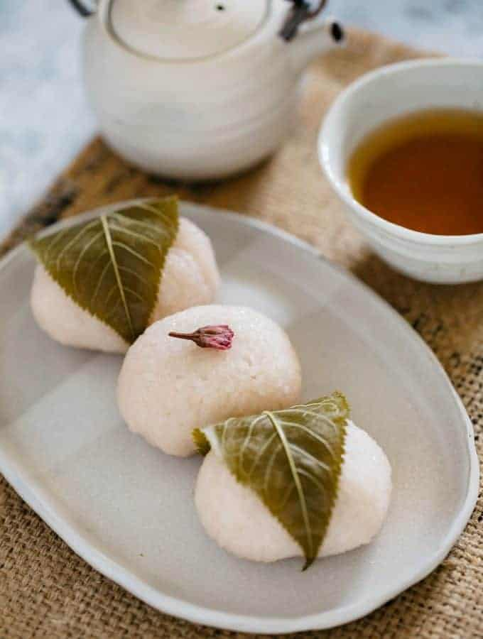 Two sakura mochi with leaves wrapped around, one sakura mochi decorated with one flower on top of it.