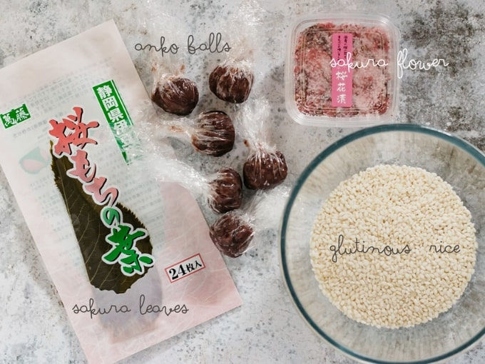 sakura leaves in a commercial packet, 6 anko balls, glutinous rice in a medium bowl, salted sakura flower in a container