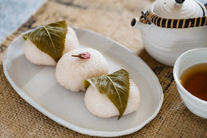 Two sakura mochi wrapped with sakura leaves around, and one in the middle without sakura leaves but a sakura flour.