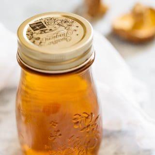 Shiitake dashi in a storing jar with two dried shiitake mushrooms in background