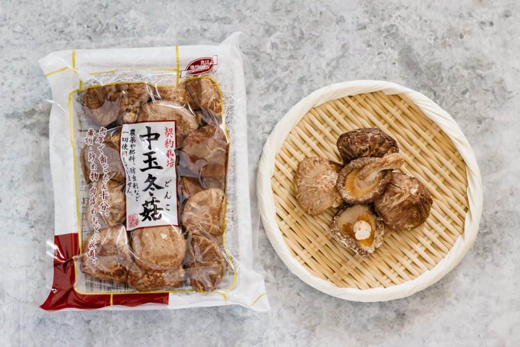 dried shiitake mushroom packet and dried shiitake mushrooms on a bamboo tray on the right