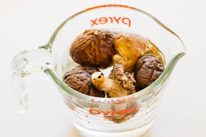 Dried shiitake mushrooms in water in a jug.