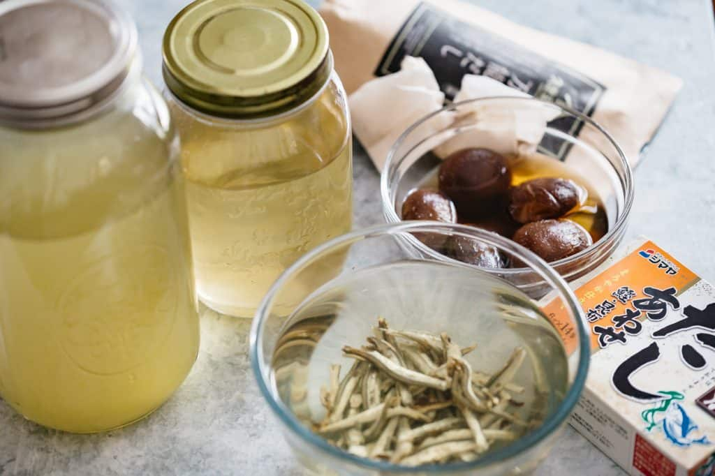 Two dashi in jars, dried infant anchovies and shiitake mushrooms in bowls, and dashi pack in background