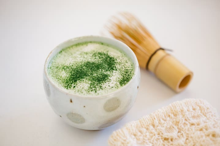 matcha latte served in a Japanese tea bowl with a bamboo whisk in background