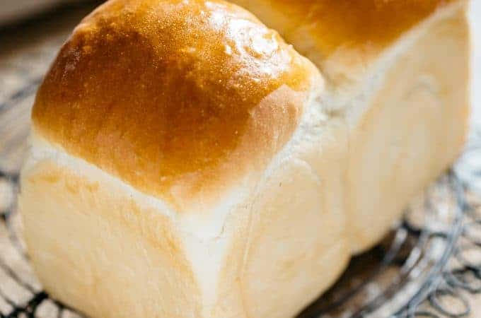 a freshly baked shokupan Japanese milk bread loaf on a cooling rack