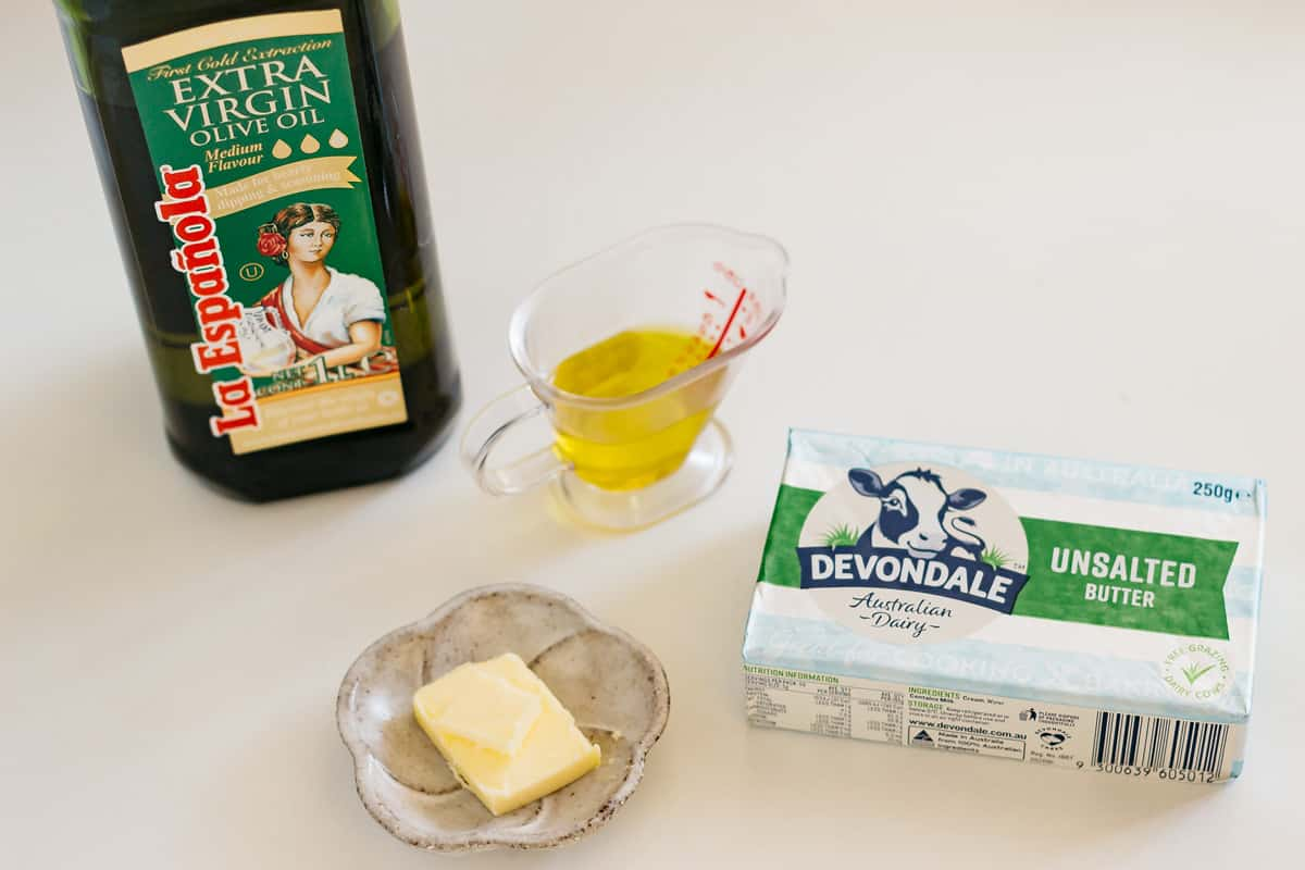 unsalted butter on a small plate and butter package on the right and olive oil on the left