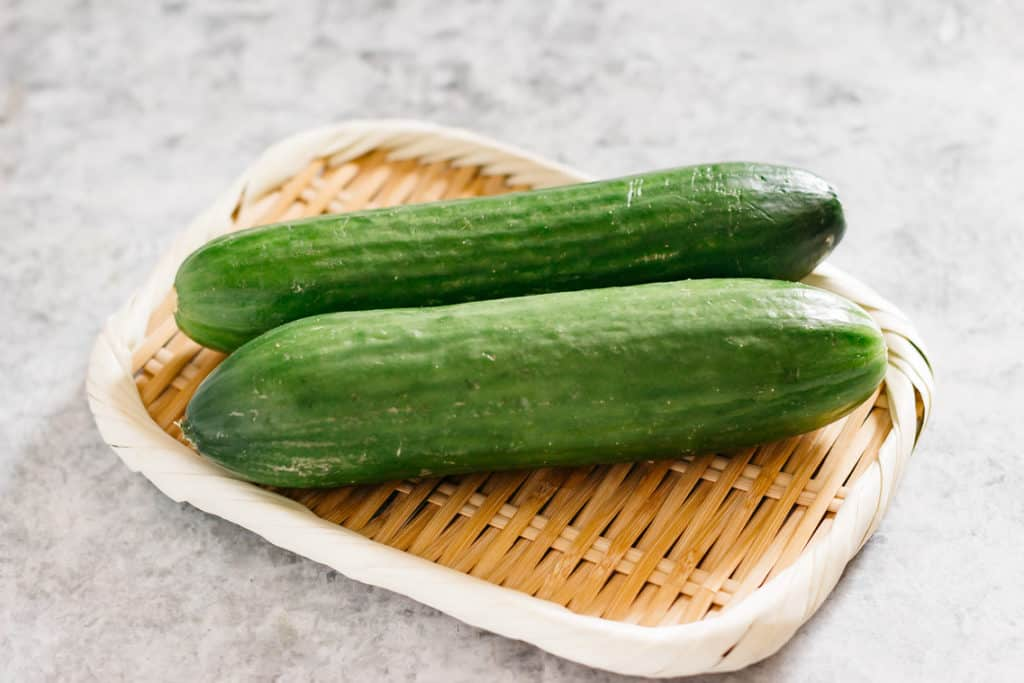 two Lebanese cucumbers on a bamboo tray