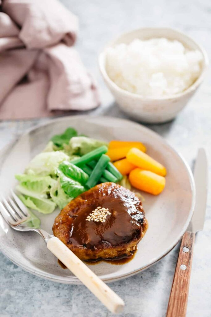 A Japanese hamburger steak served on a round plate with green salad veggies and carrots and green beans.