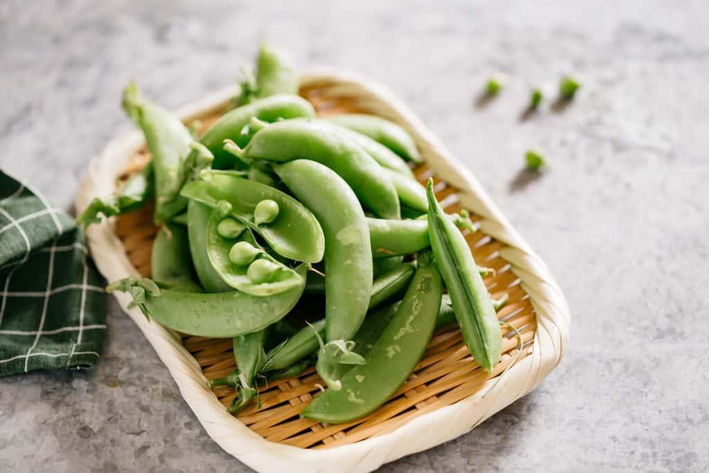 fresh garden peas on a bamboo tray