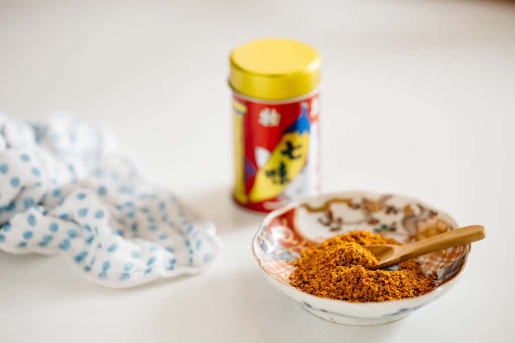 shichimi togarashi in a small bowl with the container in background