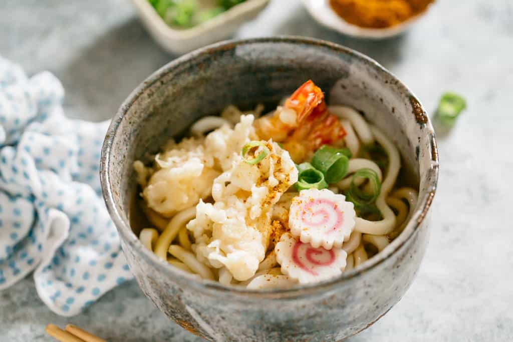 Tempura Udon served in a Japanese pottery bowl with two shrimp tempura