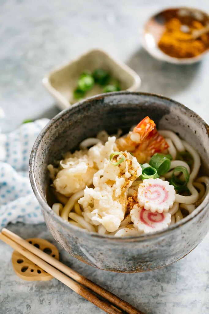 Tempura Udon served in a Udon noodle soup bowl with two shrimp tempura, two slices of Naruto and scallions.