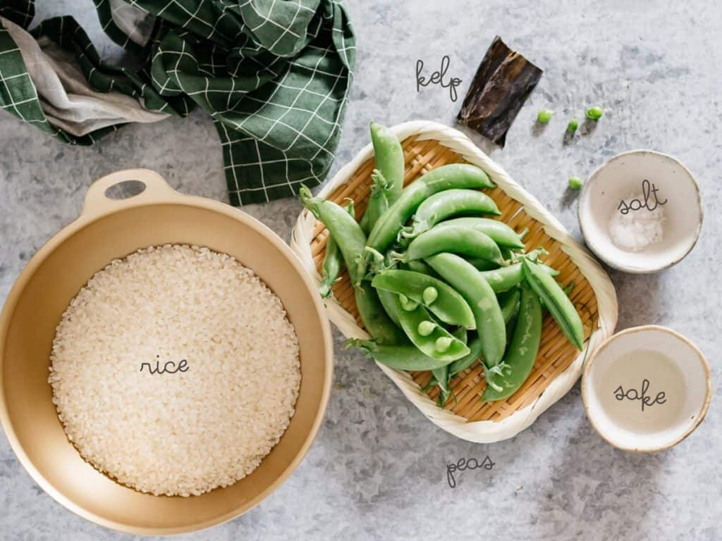 Uncooked Japanese Koshihikari rice, sugar snap peas, salt in a small bowl, sake in a small bowl and a strip of dried kelp