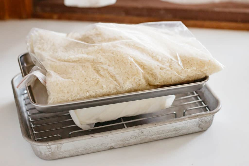 a tofu piece wrapped with a sheet of kitchen towel with a weight over the tofu to remove water