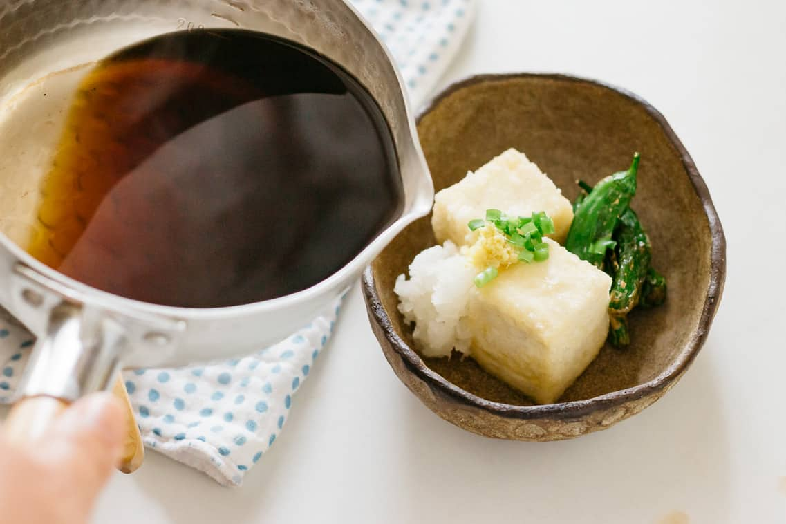 Agedashi tofu served on an oval bowl and tsuyu in a saucepan