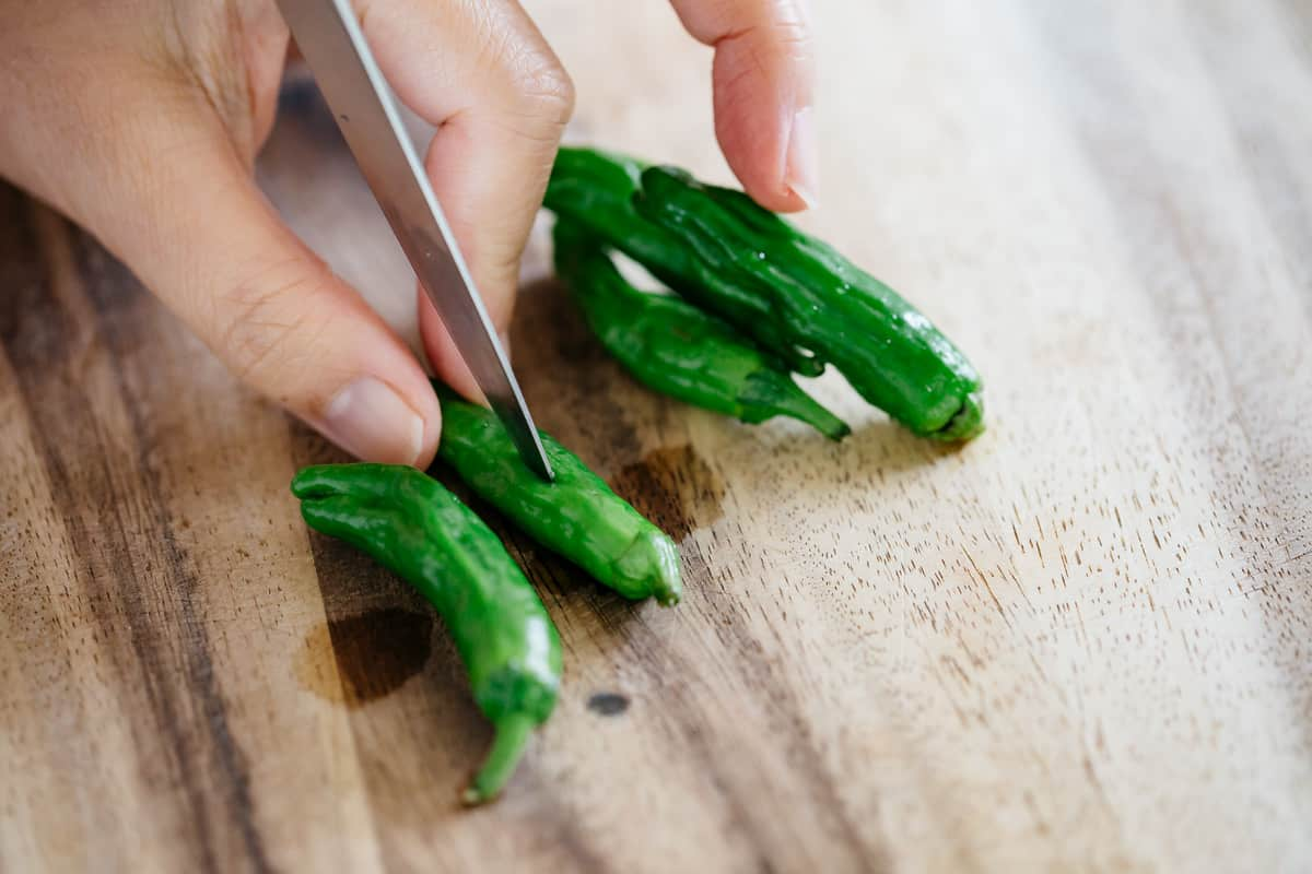 Poking shishito peppers with a knife