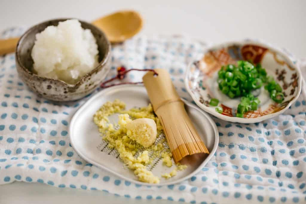 Grated daikon in a small bowl, grated ginger, and finely chopped scallions