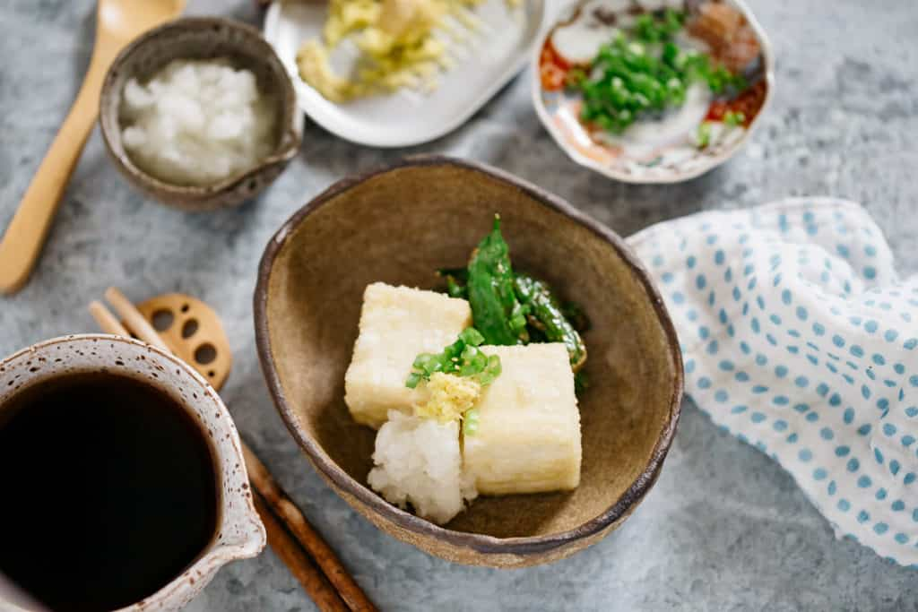 Agedashi tofu in a oval bowl, surrounded by bowls of garnishes and sauce