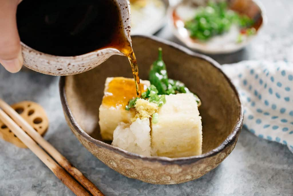 Agedashi tofu served on an oval bowl and Tsuyu sauce being poured over