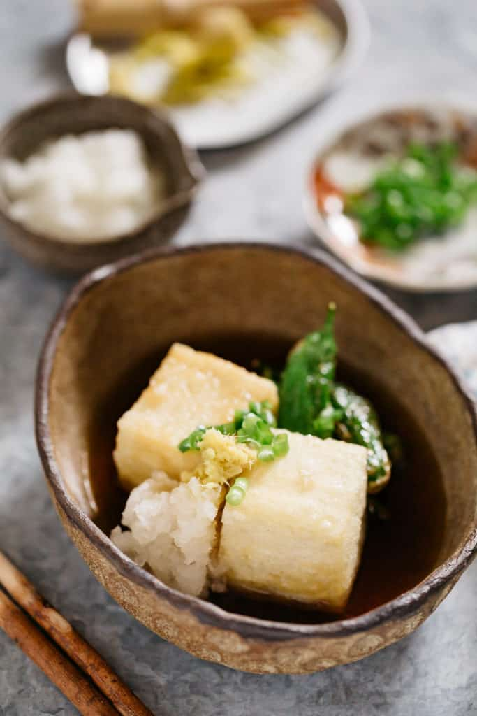 Two Agedashi tofu served in a oval bowl with garnishes and tsuyu