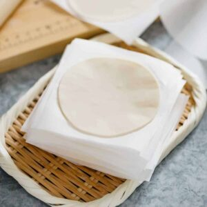 a stack of gyoza wrappers on a bamboo tray