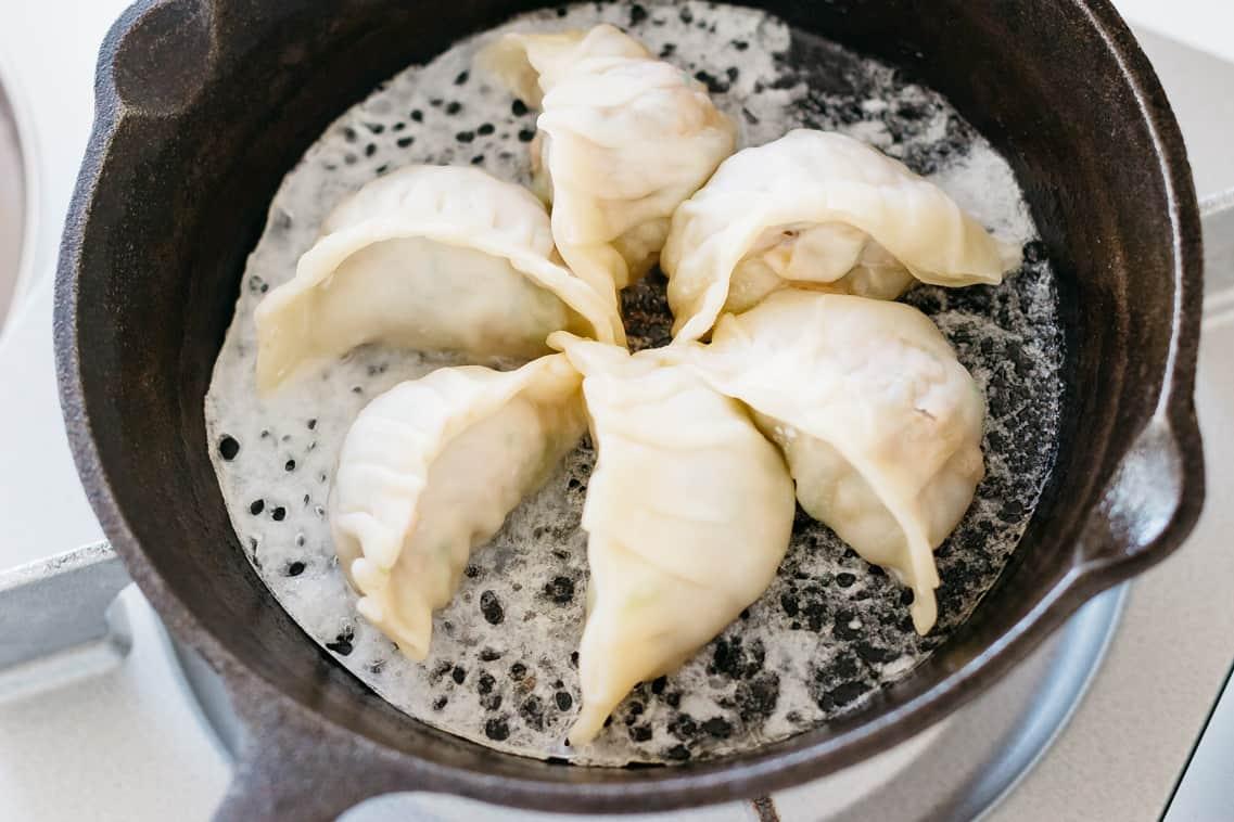 6 gyoza dumplings in a steel skillet