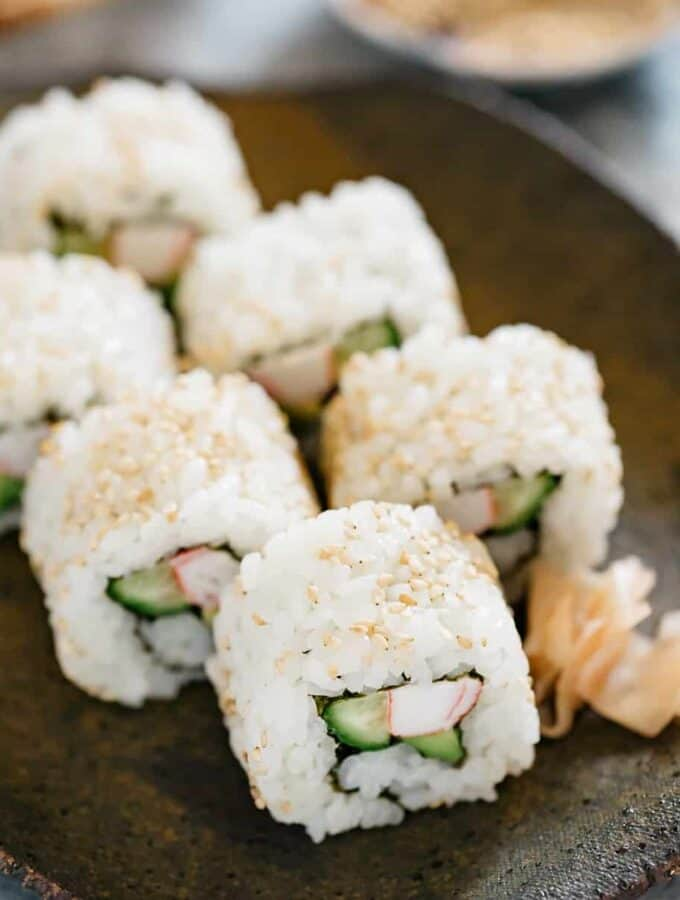 6 pieces of California roll is on a black plate