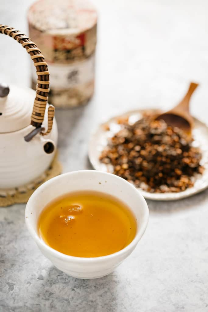hojicha in a small cup and a teapot in background
