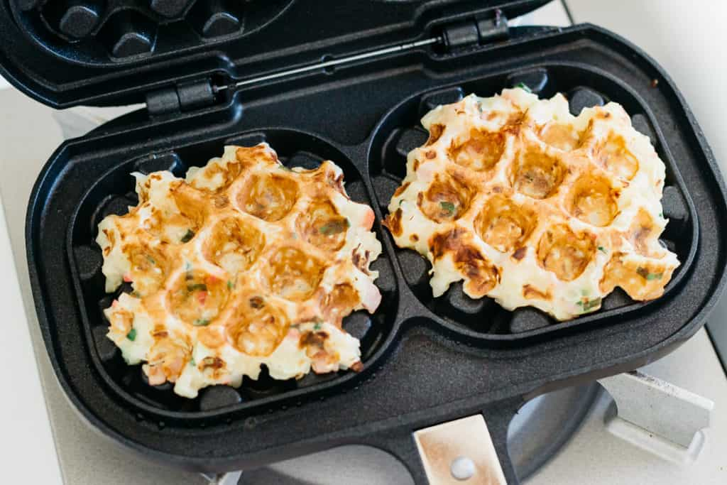 Okonomiyaki savory waffles being baked on a waffle iron over a stove top