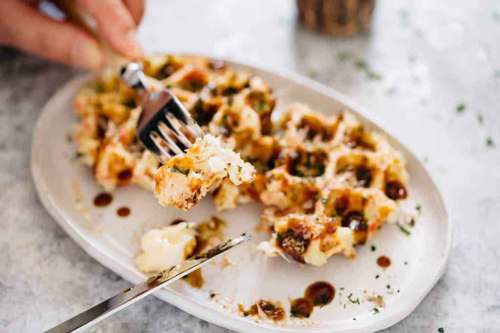 Two okonomiyaki savory waffle served on an oval plate with a folk and a knife