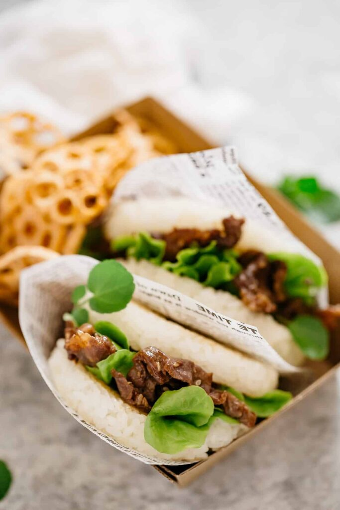 two serves of sushi burger with Yakiniku on a take away cardboard plate with renkon chips