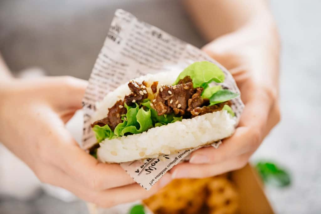 hands holding a sushi burger with yakiniku