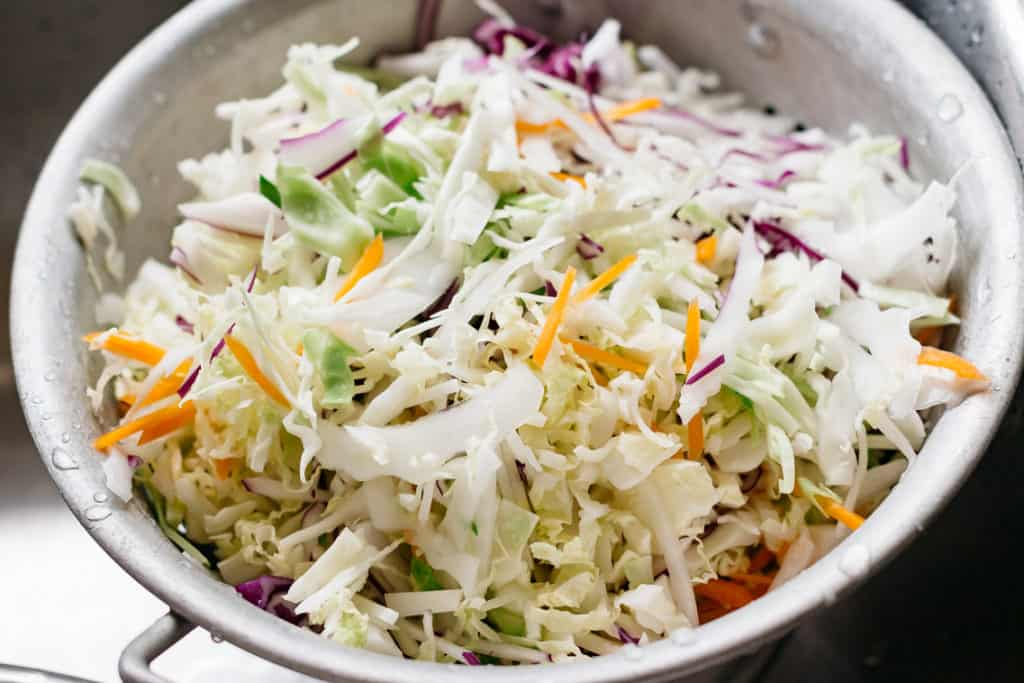 Asian slaw ingredients, cabbages are being washed and in a colander