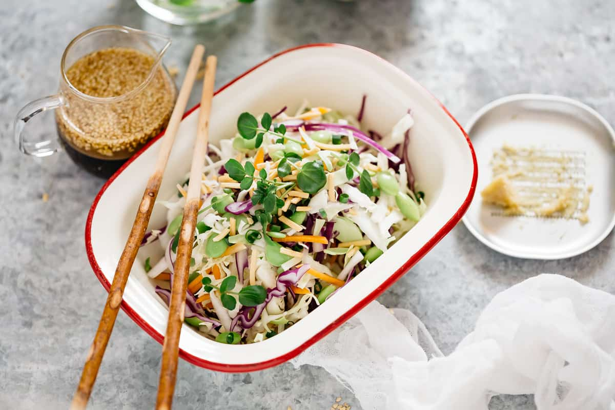 Asian slaw salad served in a rectangle dish with the sesame soy dressing jug